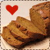 a loaf of pumpkin bread with several slices cut from it and a heart shape